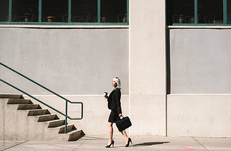Stylish businesswoman walking in the city by Simone Becchetti for Stocksy United