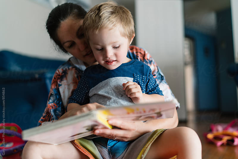 Mother reading to her Child on the Floor by Gary Radler Photography for Stocksy United