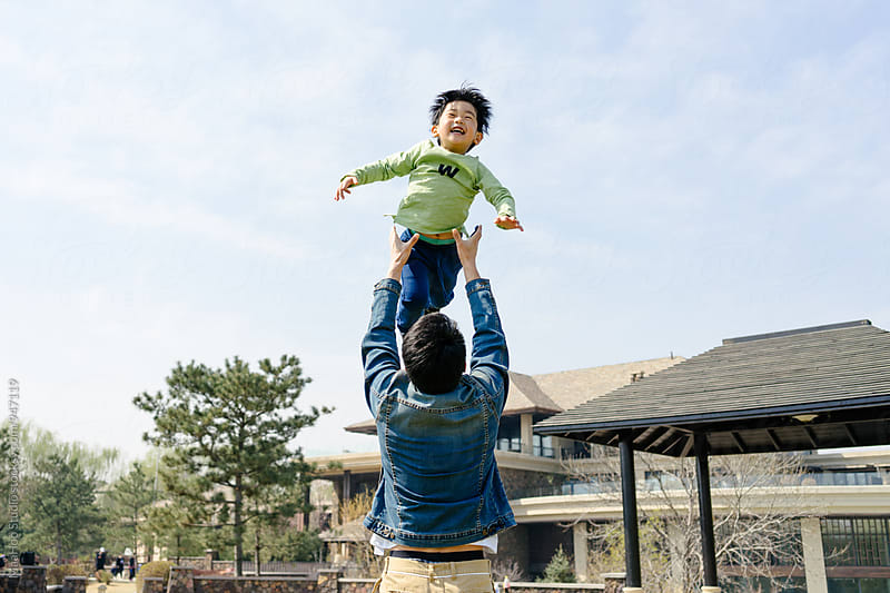 Young father playing with his child by throwing him  in the air by MaaHoo Studio for Stocksy United