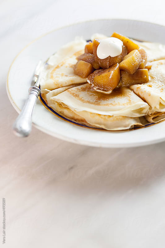 Thin pancakes with apples and cream by Vera Lair for Stocksy United