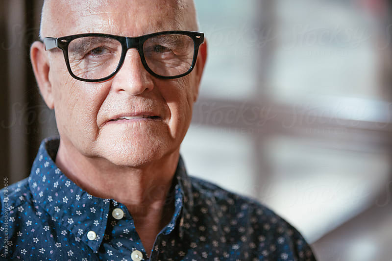 Trendy senior man portrait, wearing glasses and a dark blue shirt looking at the camera. by Inuk Studio for Stocksy United