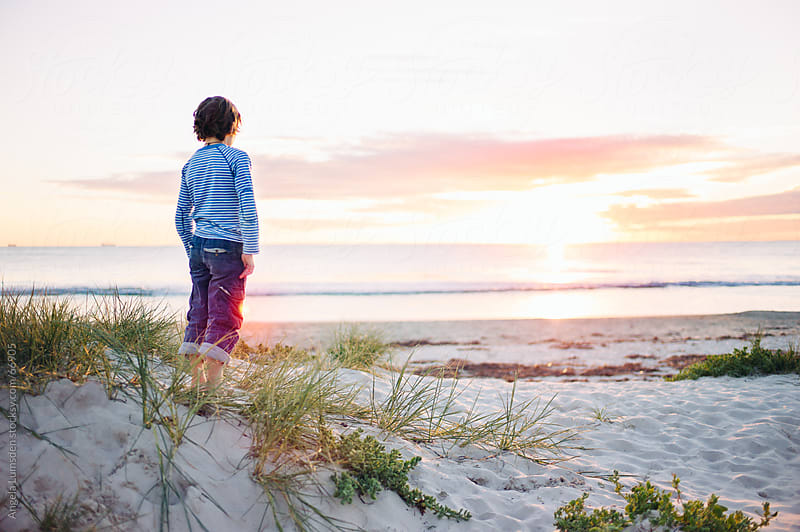 Boy watching the sunset over the ocean by Angela Lumsden for Stocksy United