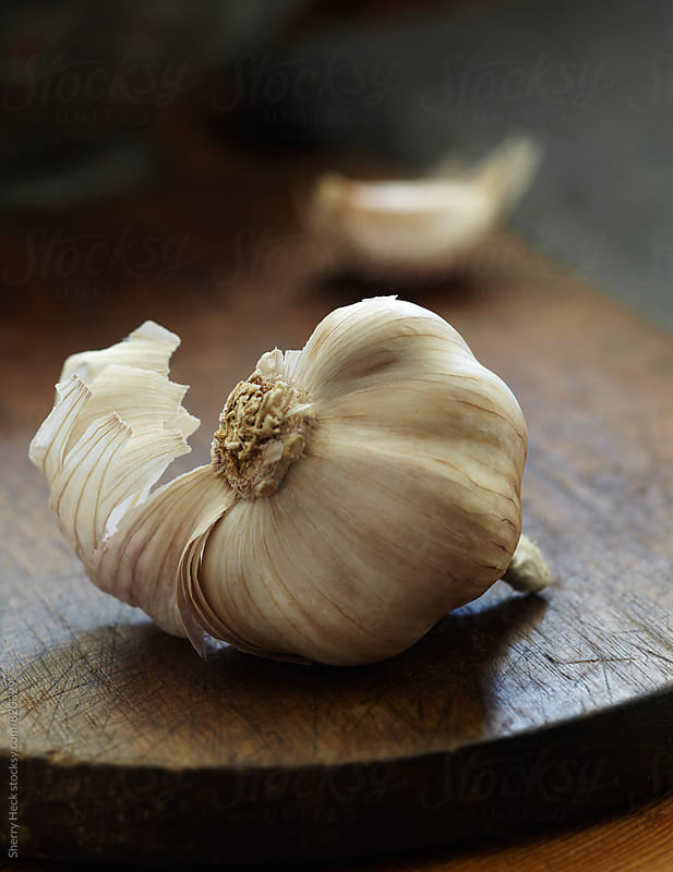 Bulb of garlic resting on cutting board with tear of garlic skin visiable by Sherry Heck for Stocksy United