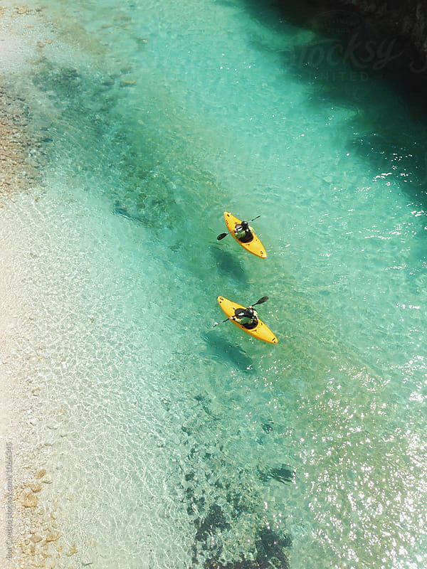 Two kayaks in blue water by Bor Cvetko for Stocksy United