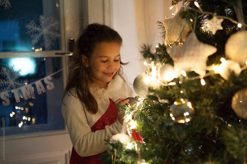 Girl Decorating the Christmas Tree by Lumina for Stocksy United