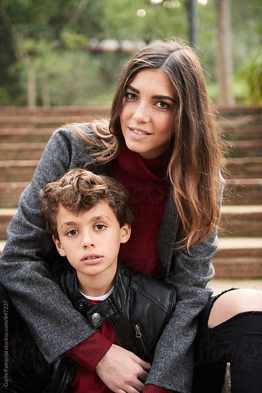 Serious boy and smiling young mother looking at camera while sitting on steps by Guille Faingold for Stocksy United
