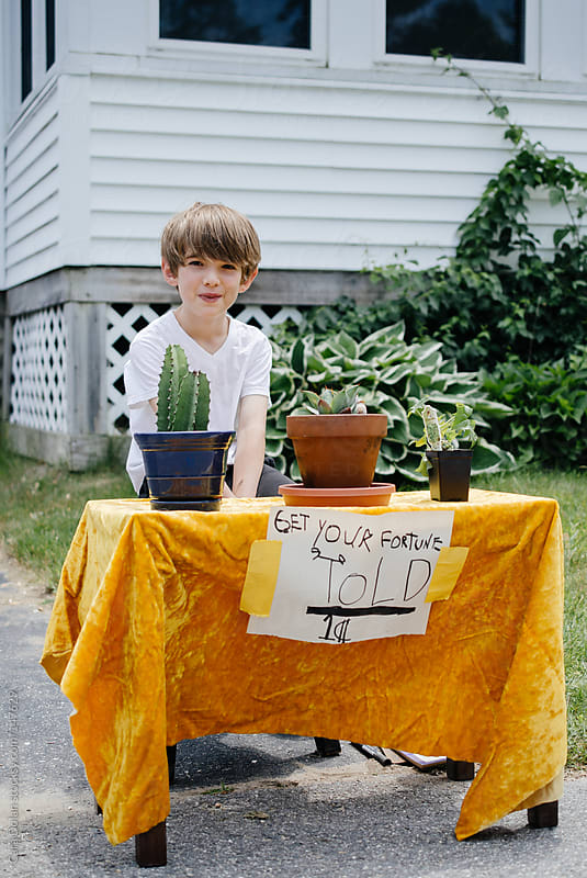 Little boy sells fortunes for one cent by Cara Dolan for Stocksy United