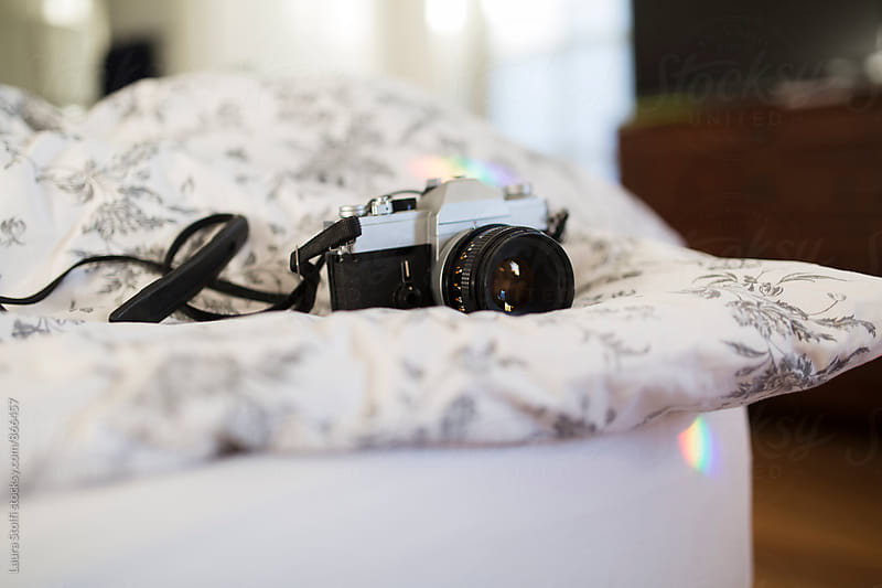 Vintage analogical camera on flowered duvet in bright bedroom with rainbows by Laura Stolfi for Stocksy United