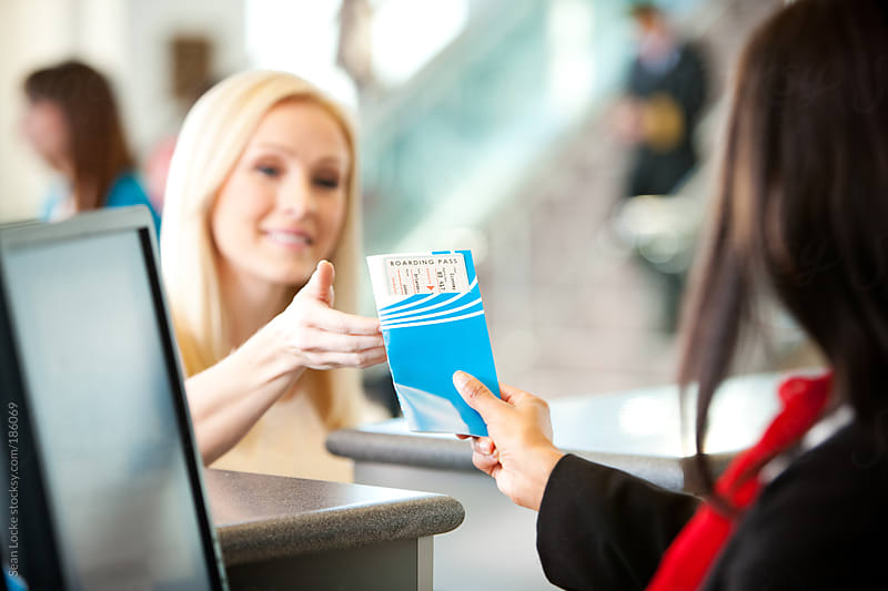 Airport: Ticket Agent Hands Ticket to Customer by Sean Locke for Stocksy United