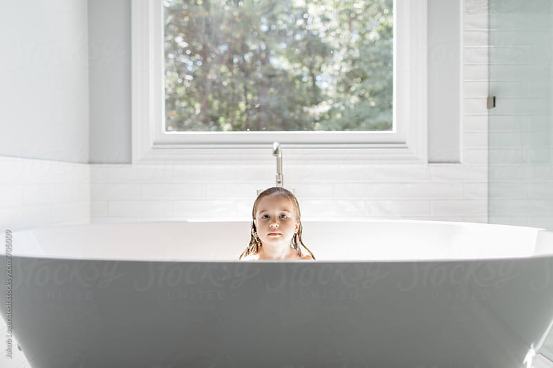 A beautiful young girl peeking out from a large bathtub by Jakob for Stocksy United