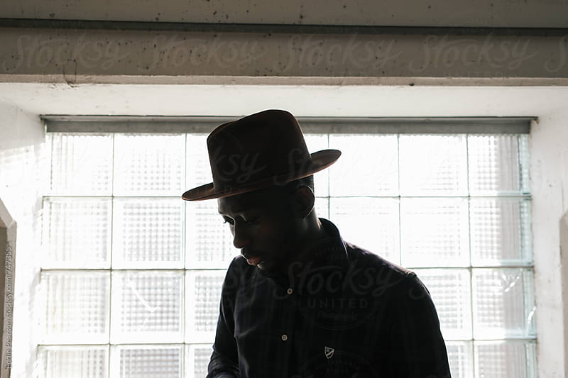 Silhouette of a dapper man standing in front of a window by Eddie Pearson for Stocksy United