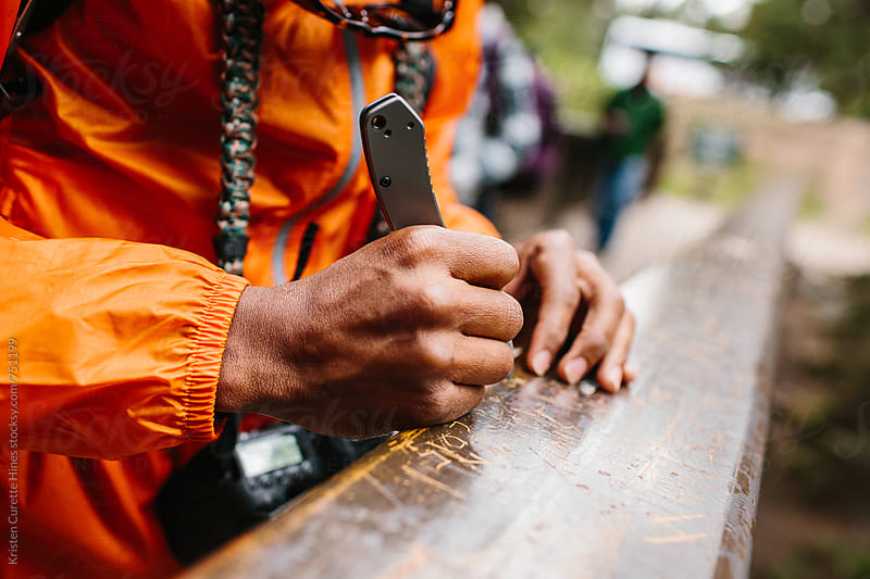 A man carving his name into a bridge in the woods by Kristen Curette Hines for Stocksy United