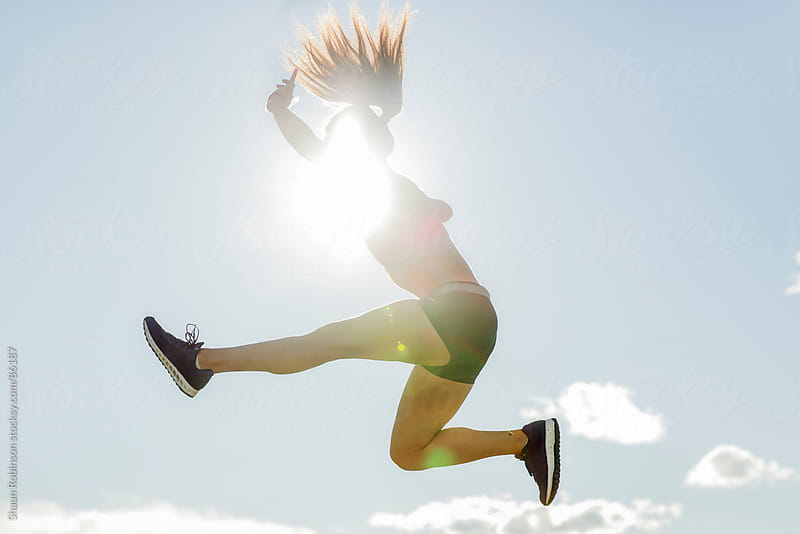 a woman in workout clothes jumping through the sky by Shaun Robinson for Stocksy United