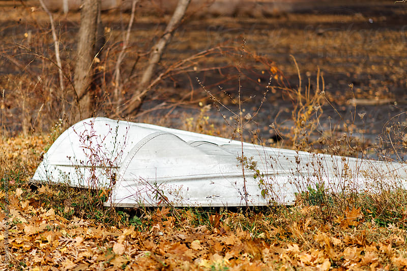 old boats on shore in autumn by Deirdre Malfatto for Stocksy United