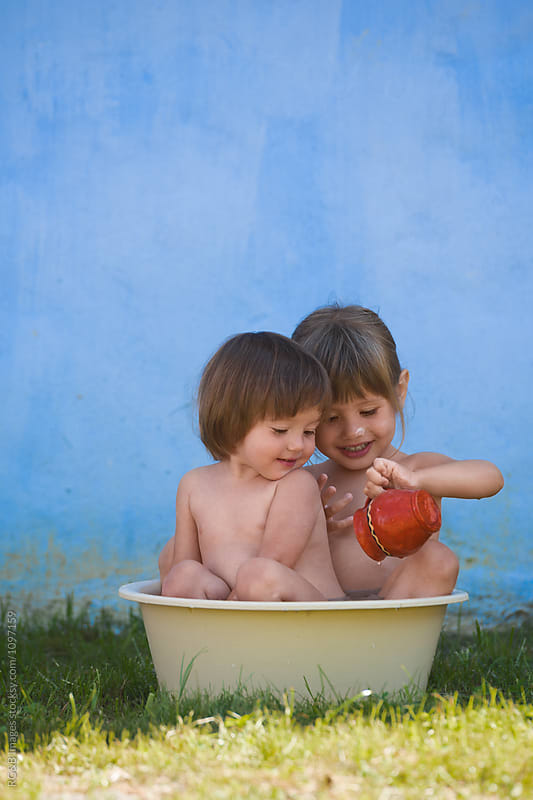 Little sisters bathing together in a plastic basin outside by RG&B Images for Stocksy United