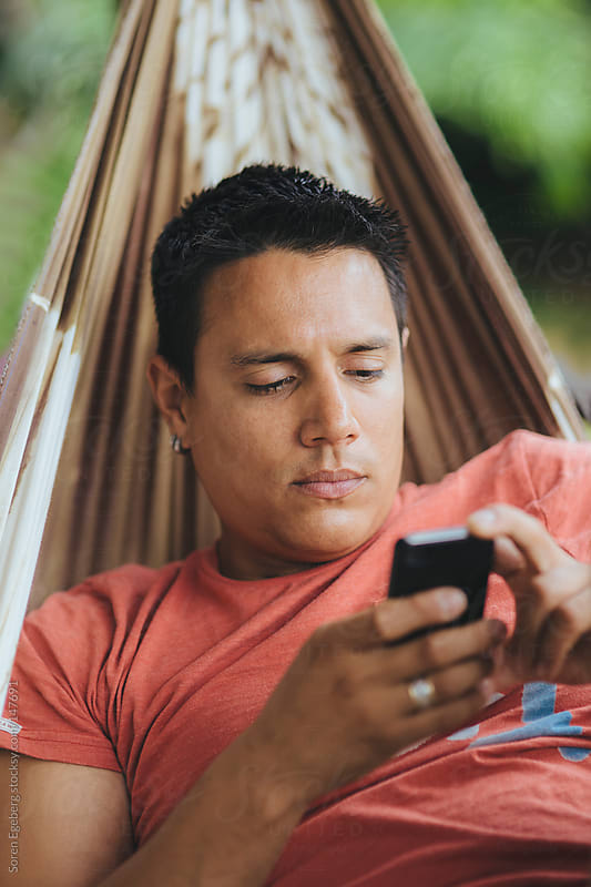 Portrait of man lying in hammock using mobile smart phone. by Soren Egeberg for Stocksy United