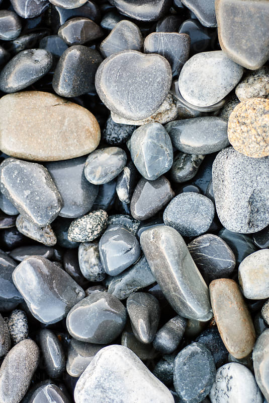 Smooth, rounded beach stones by Cara Dolan for Stocksy United