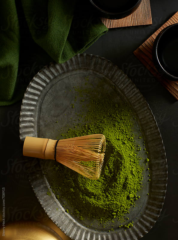 Green matcha powder with bamboo whisk on pewter plate by Sherry Heck for Stocksy United