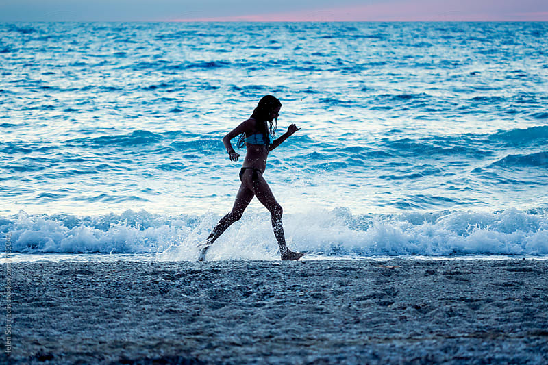 Young Woman Runs on the Beach at Twilight by Helen Sotiriadis for Stocksy United