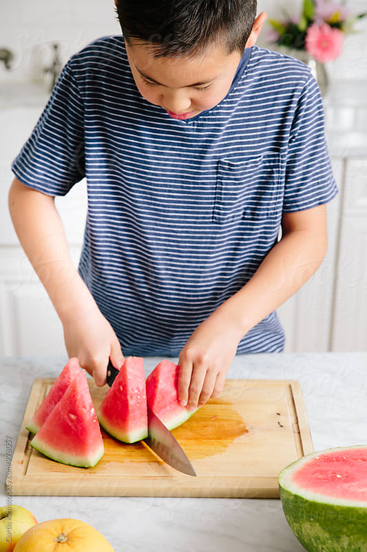 Kid slicing up watermelon by Curtis Kim for Stocksy United