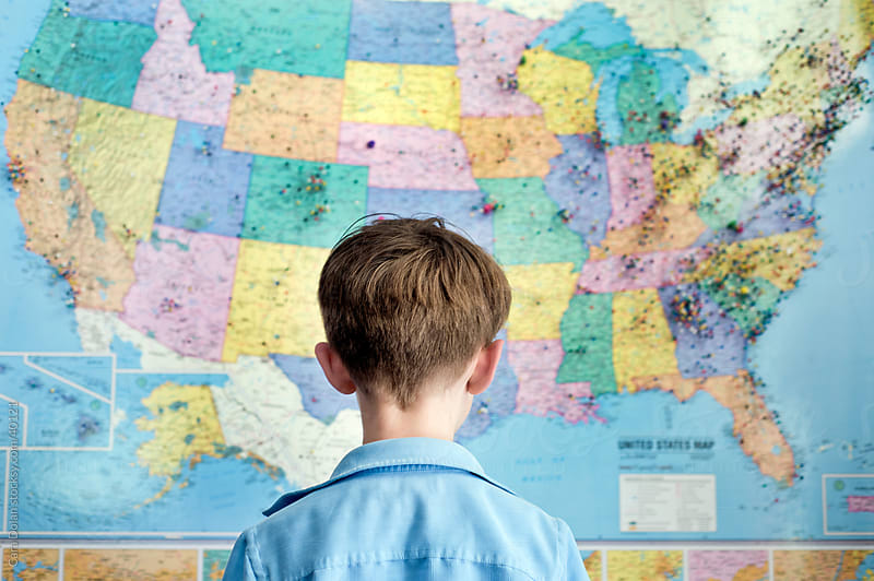 Boy stands looking at a map of the United States by Cara Slifka for Stocksy United