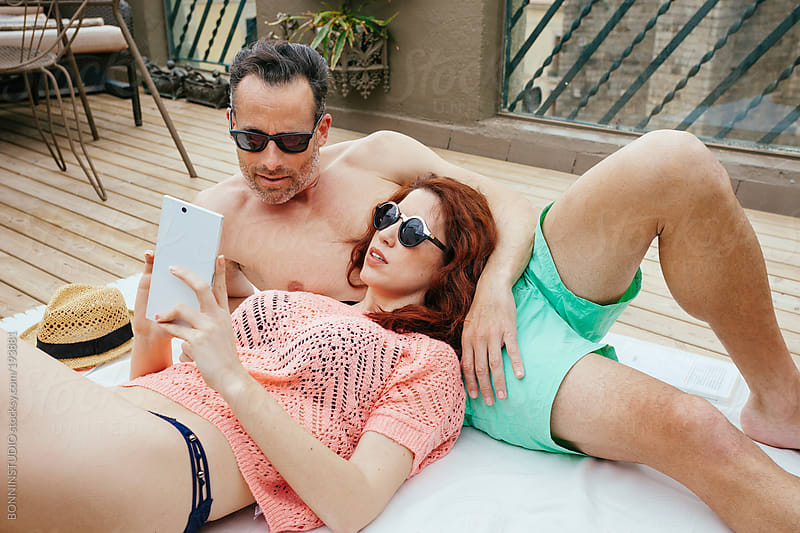 Beautiful young couple  with smart phone on his terrace. Summer time. by BONNINSTUDIO for Stocksy United