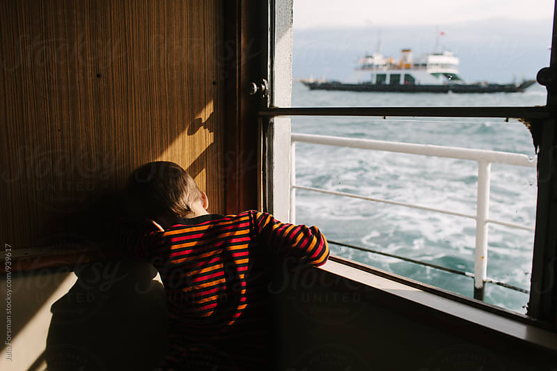 Boy rests his head in a shaft of sunshine while travelling by ferry. by Julia Forsman for Stocksy United