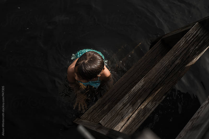 Child Sitting On Ladder In Lake by Alison Winterroth for Stocksy United