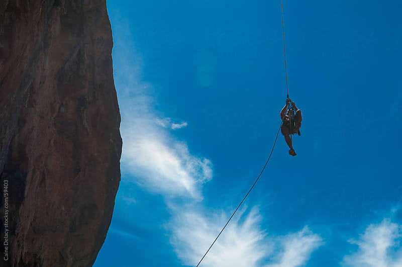 A climber ascends a rope on a cliff face by Caine Delacy for Stocksy United