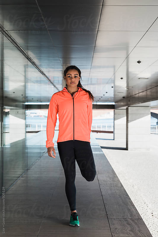 Young mixed race woman athlete stretching outdoors by Lior + Lone for Stocksy United