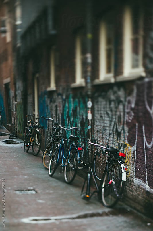 Bicycles left in a alley. by Javier Pardina for Stocksy United