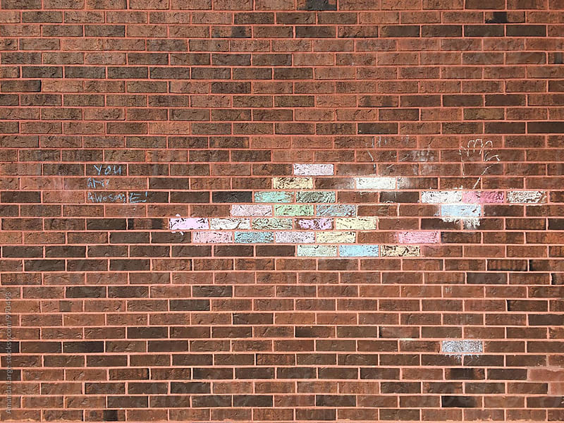 chalk design on a red brick wall by Amanda Large for Stocksy United