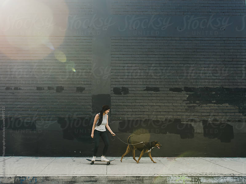 Young woman skating with dog by Isaiah & Taylor Photography for Stocksy United