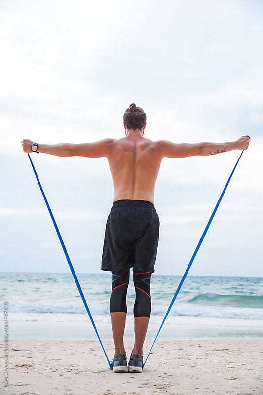 Man exercising at the beach with rubber band by Jovo Jovanovic for Stocksy United