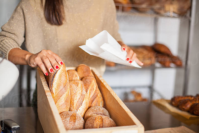 Woman Packing Bread in a Bakery by Mosuno for Stocksy United