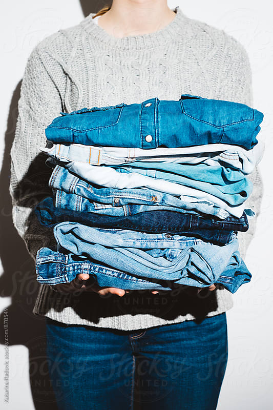 Woman Holding a Pile of Denim by Katarina Radovic for Stocksy United