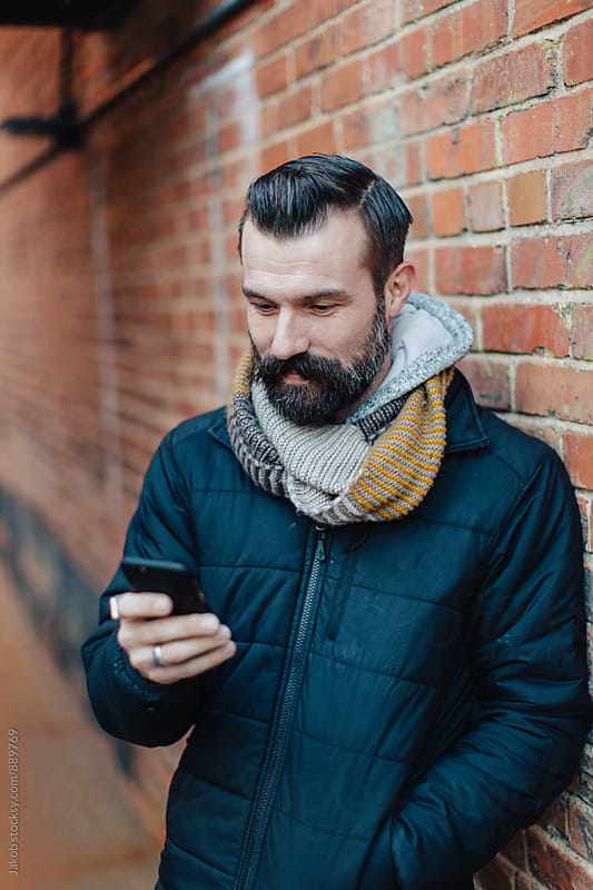 Handsome well groomed guy standing by a brick wall looking at his phone by Jakob for Stocksy United