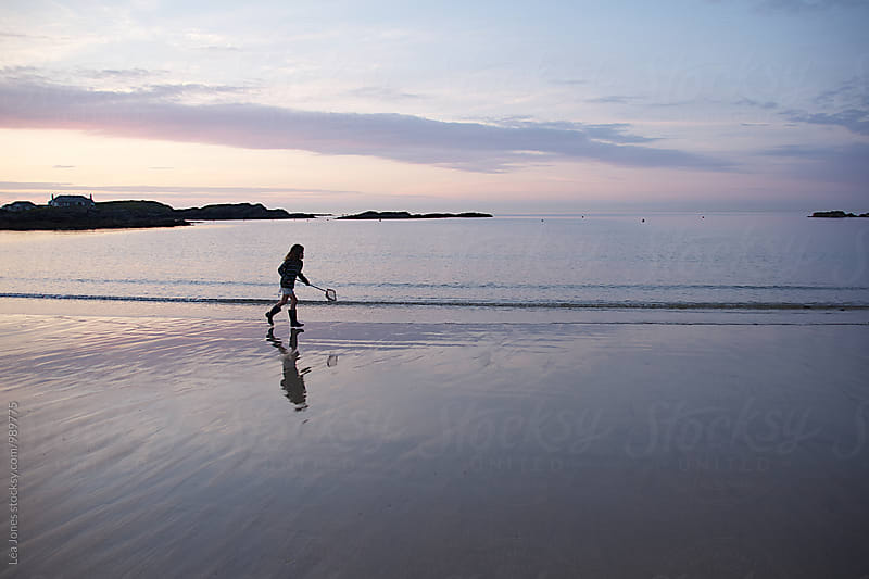 young girl with fishing net running on the beach after sunset by Léa Jones for Stocksy United