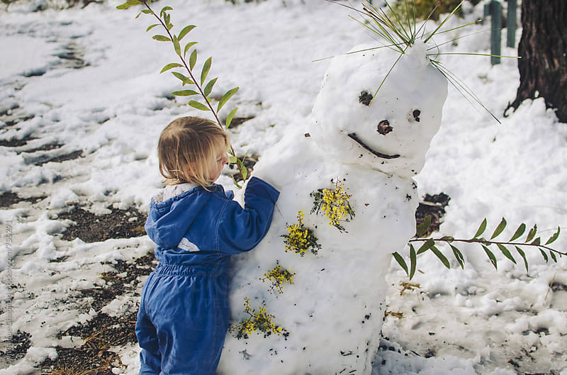 Little girl building a snow man by Dominique Chapman for Stocksy United