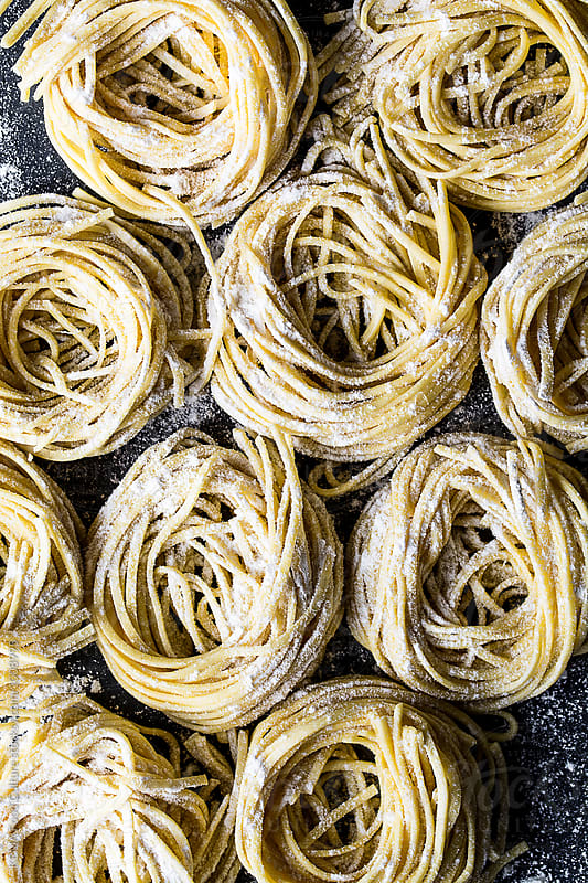 Fresh pasta on floured cement surface by KEMA Food Culture for Stocksy United