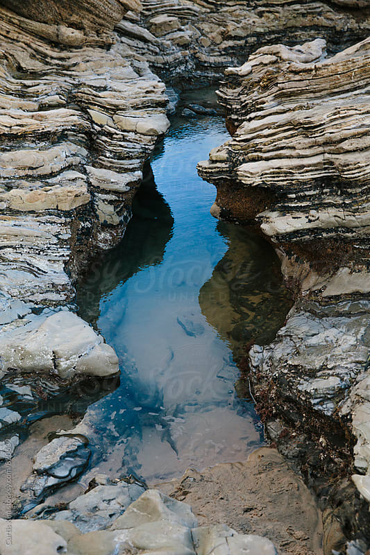 Tidal pool showing water and rocky landscape by Curtis Kim for Stocksy United