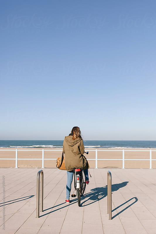 Woman on the boulevard looking to the ocean on her bike. by Koen Meershoek for Stocksy United