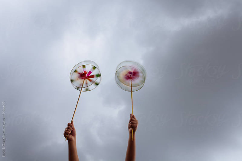 Child playing with pinwheel on a windy overcast day by Saptak Ganguly for Stocksy United