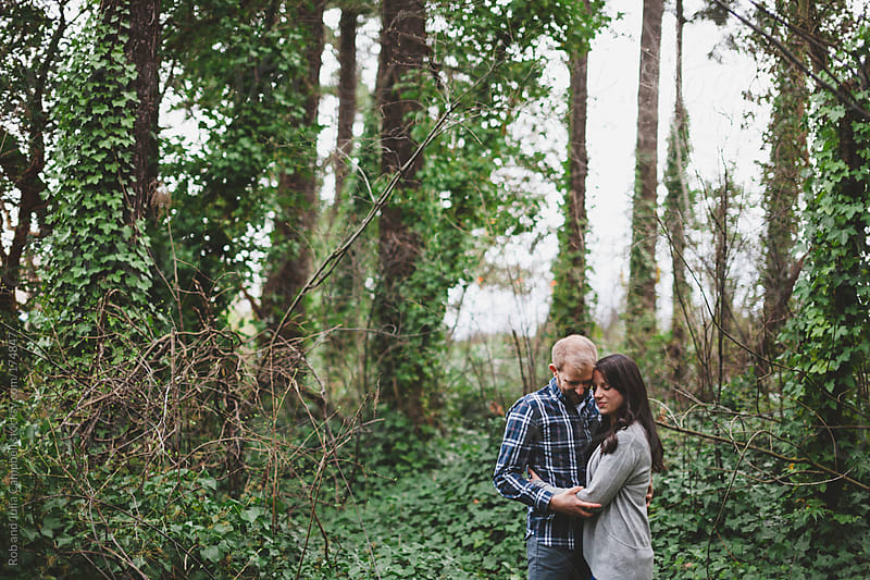 romantic couple - husband and wife - enjoying each other in ivy forest by Rob and Julia Campbell for Stocksy United