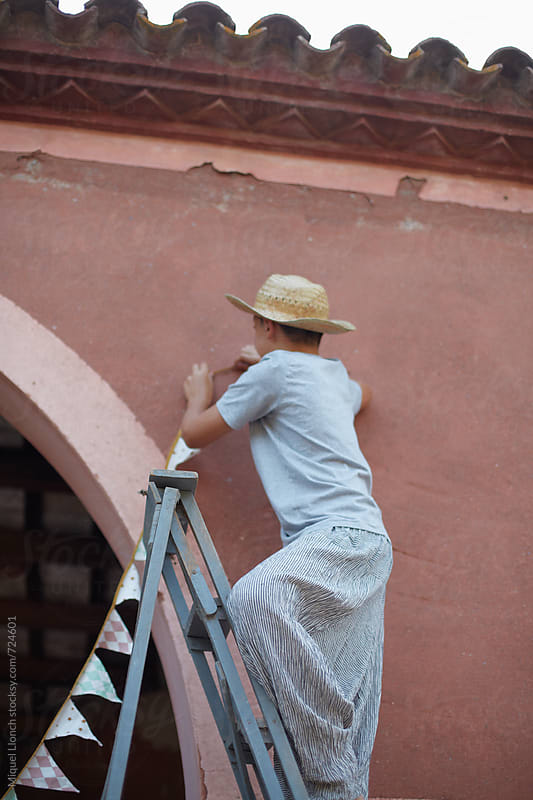 Young man on a ladder working  to hold some decoration on a red old wall by Miquel Llonch for Stocksy United