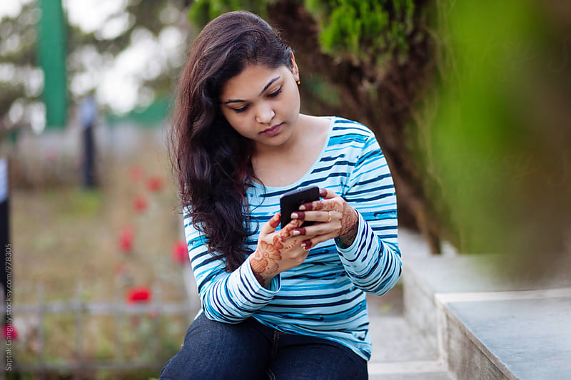 Young woman using mobile phone in the park by Saptak Ganguly for Stocksy United