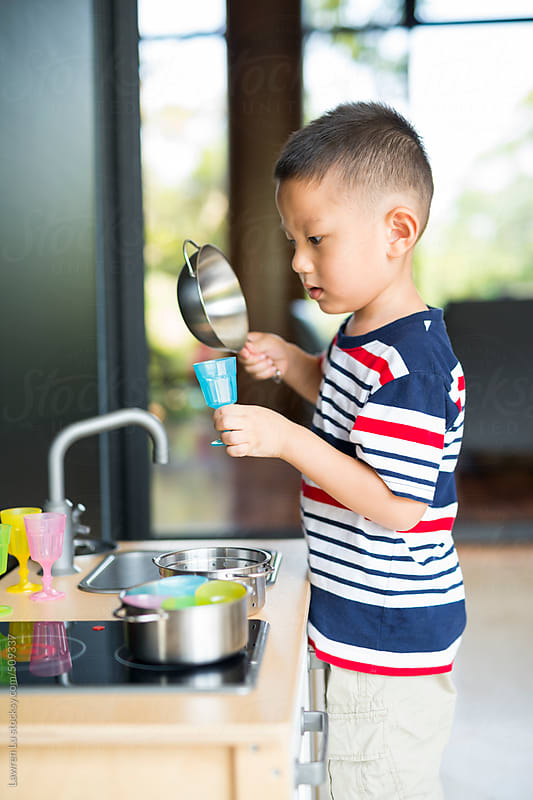 Kid imitating cooking with toy kitchen by Lawren Lu for Stocksy United