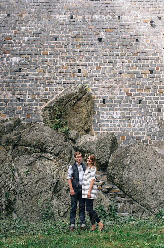 Couple is standing in front of wall in the park by Tomas Mikula for Stocksy United