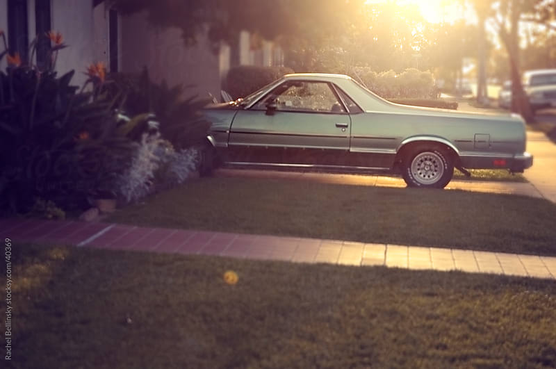 An El Camino vintage car sits in a sunlit California driveway by Rachel Bellinsky for Stocksy United