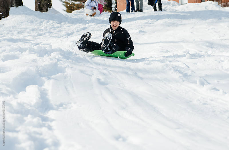 Child squeals with happiness while sledding down a hill in winter by Cara Dolan for Stocksy United